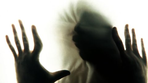 The distorted face of a young woman appears as a shadow behind a white fabric screen, with four hands touching the screen. Symbolic silhouette: fear, dream, nightmare. Close-up shot.