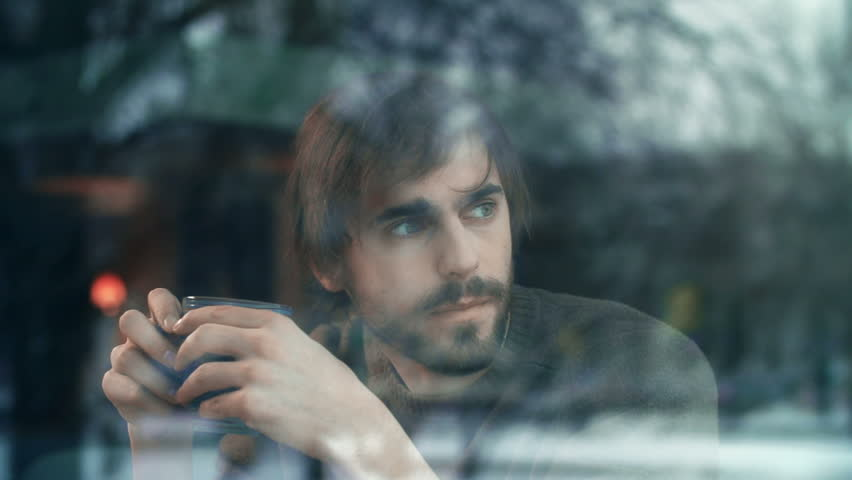 Pensive guy with cup of tea looking through the cafeteria window