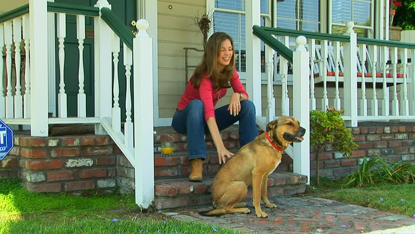 Young woman sitting on front porch petting her dog