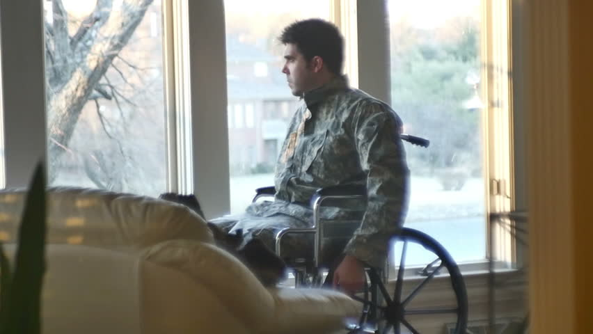 A sad veteran in camo and a wheelchair