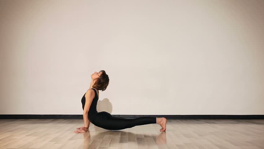 Beautiful Female In Black With Pendent Performing Yoga Asanas On The Floor. Downward  Dog   HD
