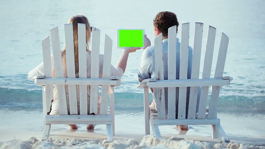 Young couple sitting back in the wooden chaise-longues on the beach. They holding tablet computer with green screen and looking at it
