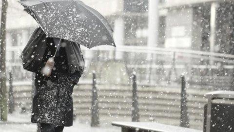 Man with umbrella in heavy snow on walking street.