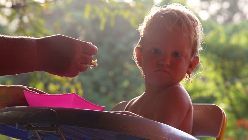 Small blonde baby girl feeding on the high chair at sunrise | Shutterstock HD Video #8631601