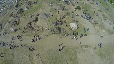 NELIDOVO - JUL 12, 2014: Many people walk by military camp during reconstruction Battlefield at summer day. Aerial view