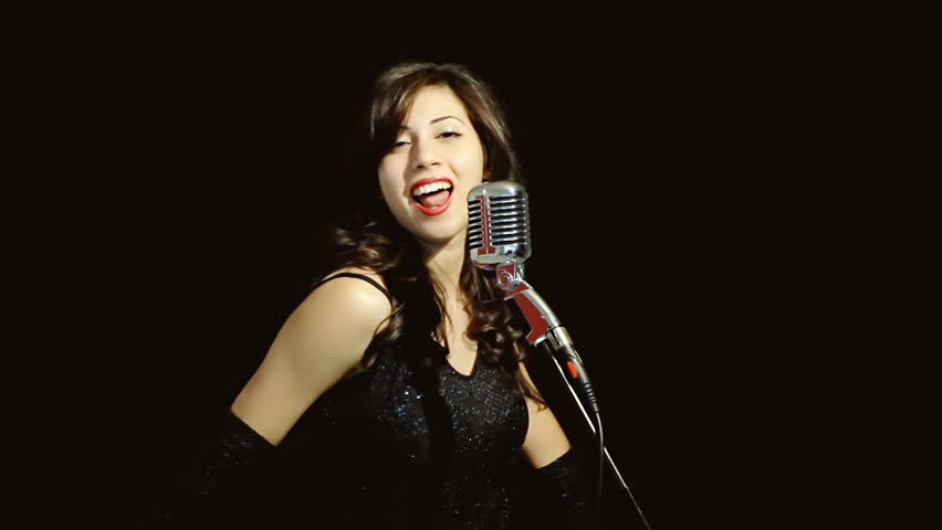 A classy young woman singing on stage with a retro vintage microphone (called Elvis or Fatty), captivating the audience with cool dance moves. Medium shot, black background.
