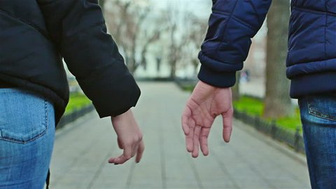 A pair of lovers walking in different directions and let their hands go. Then they join hands and walk together again.