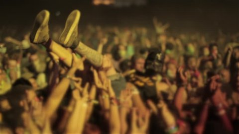 KUBANA, RUSSIA - AUGUST 1, 2013 : Young crazy fan surfing on hands crowd dancing at a music festival concert of popular rock band.