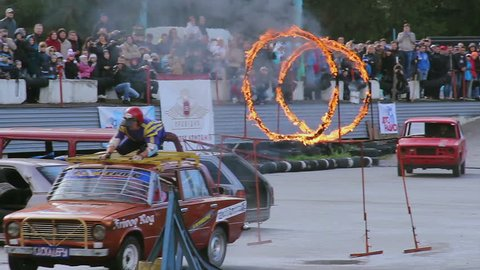 KIEV, UKRAINE - SEPTEMBER 29, 2013 - Bigfoot Crash Show. Stuntman on top of car jumps through fire circles, sequence