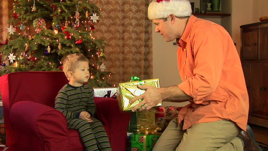 Father and little boy in pajamas opening Christmas present