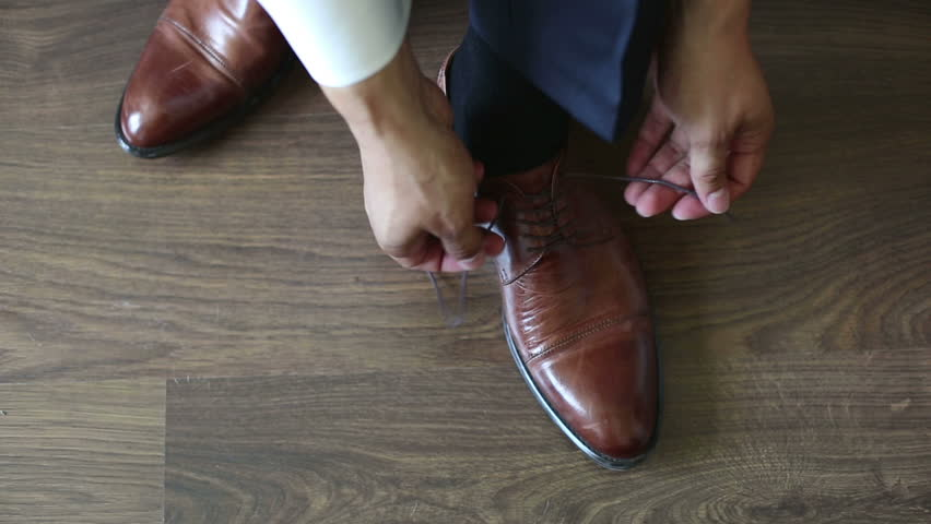 Man tying patent leather shoes formal and festive dressing.
