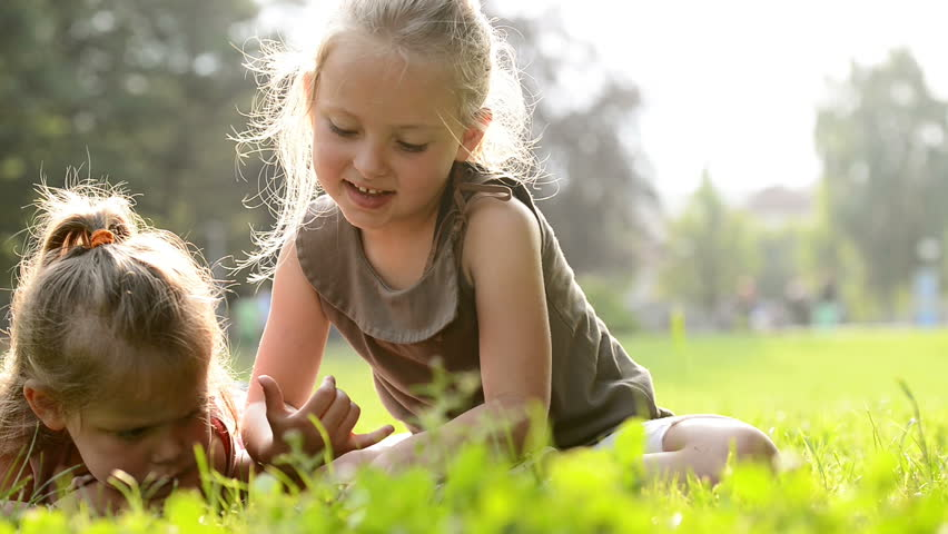 Happy blonde sisters lay down on grass are reading fairy tales on tablet at town park in summer day - HD video footage | Shutterstock HD Video #8739481