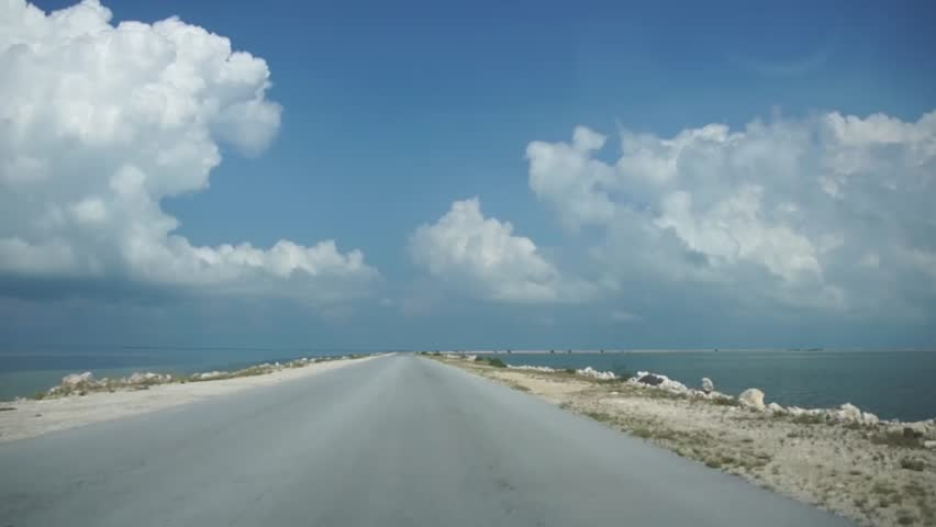 Driving up the coast keys road with water on both side beautiful blue sky with heavy clouds and Spanish music playing on the car radio going on a holiday front window cockpit driver view HD resolution
