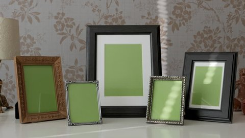 Group of Picture Frames with Green Screen on side table, tracking shot