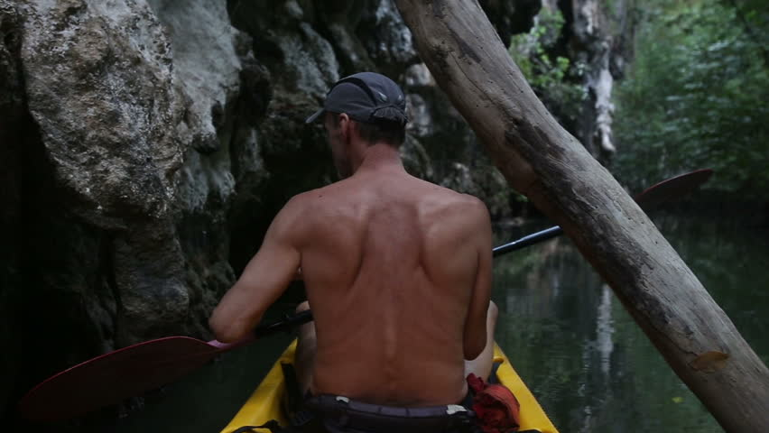 elder tanned man floating on kayak along the river near the cliff and sees monkeys #8791261