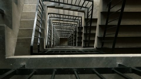 High rise concrete stairwell tracking shot. Camera tracks out over the railing of a multi storey stairwell.