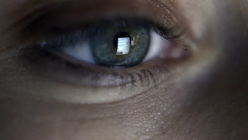 Close up of girl's eye reading internet, with reflection of screen in her eye