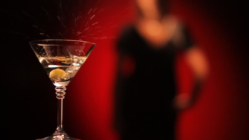 Olive falls in a glass of martini. Female silhouette on a red background