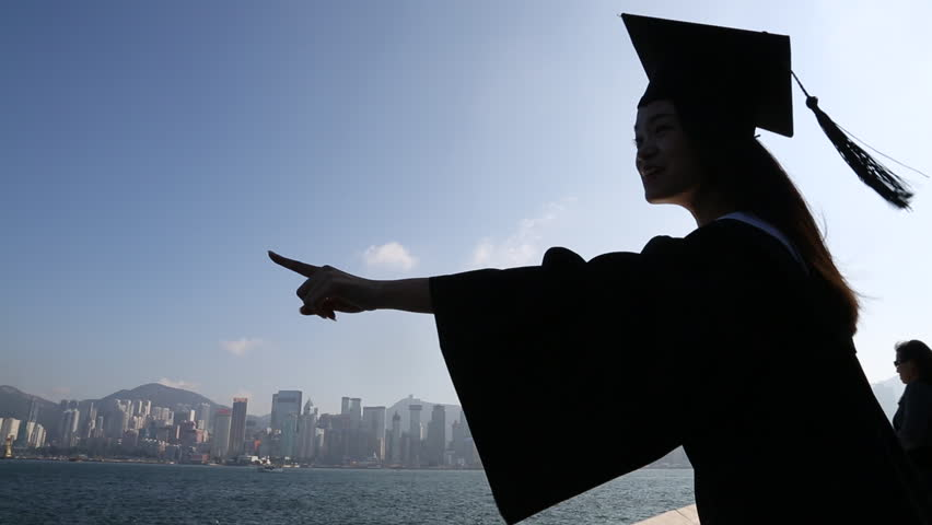 Asian woman put the Graduation cap in waterfront and look at her future front hong kong skyline on a bright sunny day -Dan | Shutterstock HD Video #8920801