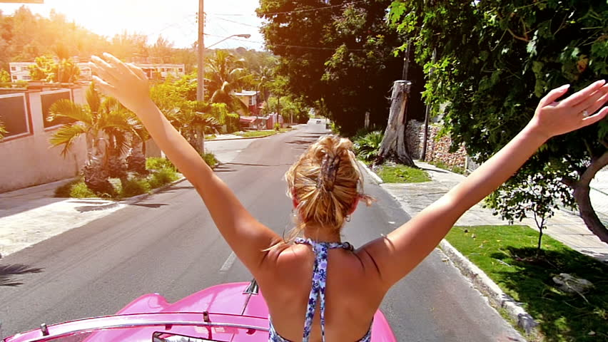 Rear view of happy blonde woman with arms outstretched, driving in pink cabriolet through Havana city, Cuba.Slow motion, high speed camera, lens flare