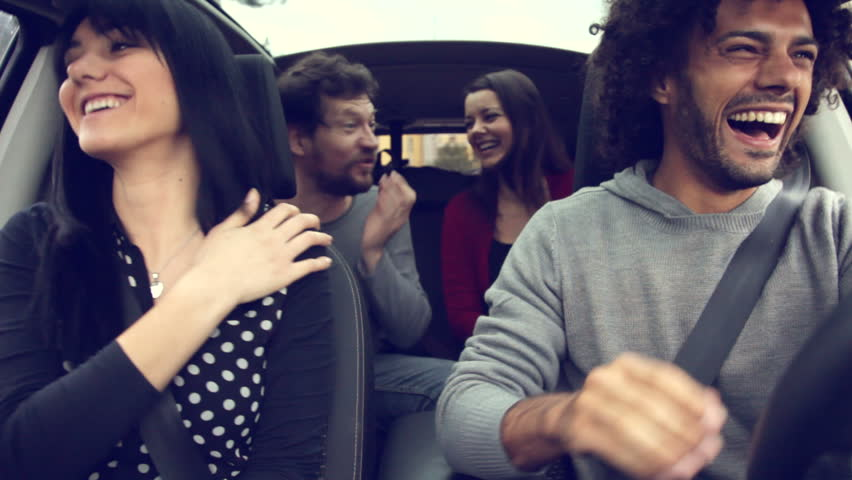 Four happy cool people having fun in car
