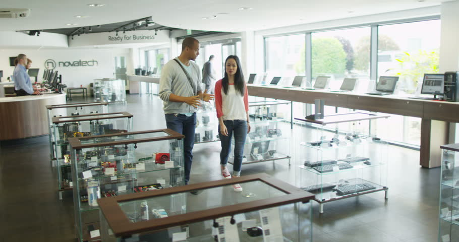 4K Couple shopping in consumer electronics store showroom