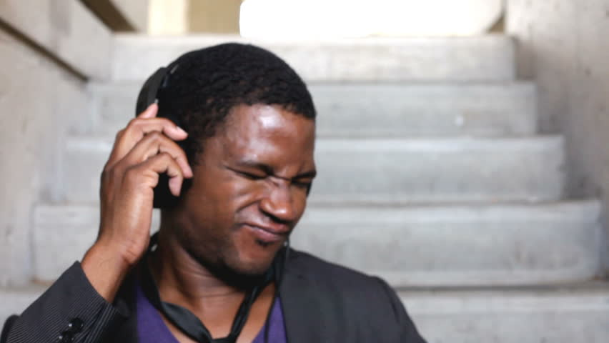 African American listening to Headphones on steps