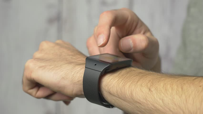 Arm of a man with a smart watch on his wrist being used.