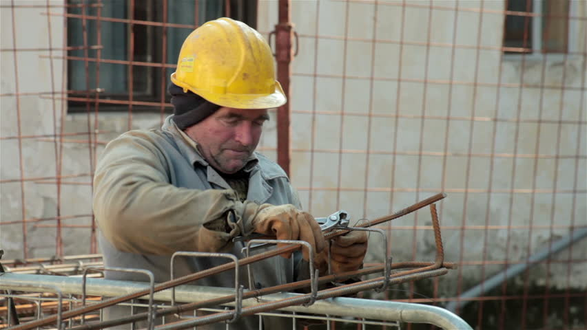 construction worker in old uniform tied armature at construction site close up elderly laborer - Construction Laborer