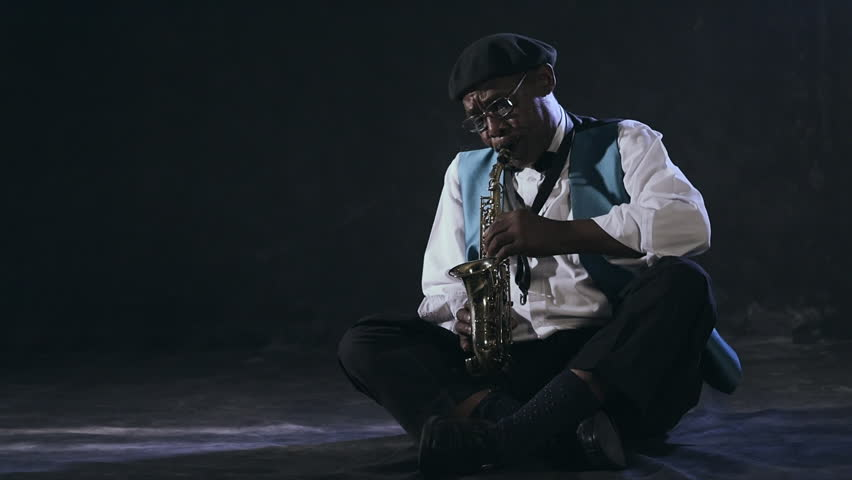 Old african black colored man playing saxophone sitting | Shutterstock HD Video #9026341