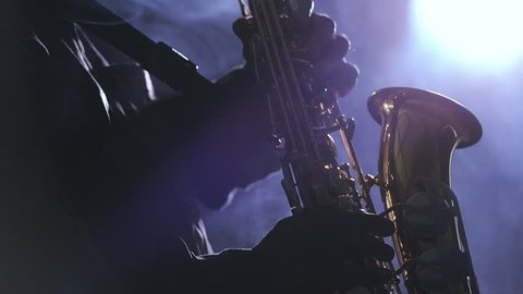 African man colored old black playing saxophone dark background music backlit silhouette