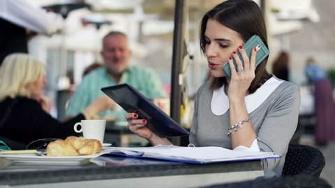Businesswoman talking on cellphone and comparing data on tablet and documents in the city
