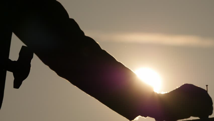 Mans hands silhouette starting hammer a nail slow motion with bright shining sun at evening | Shutterstock HD Video #9031681