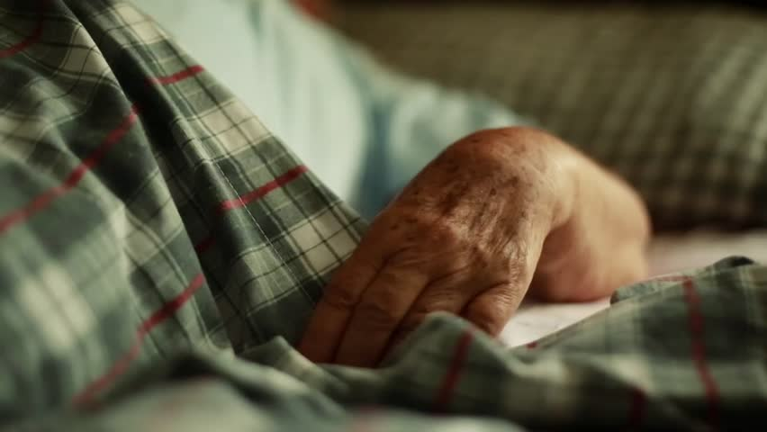 Beautiful close- up shot of Unrecognizable Elderly person's Hands as she lays down in Bed.