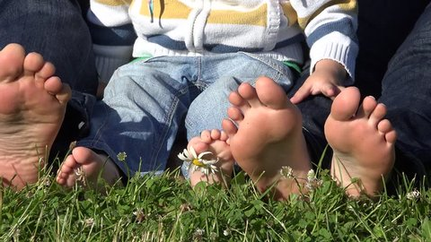 Little child and parents soles. Family bare feet on green grass. daisy flower