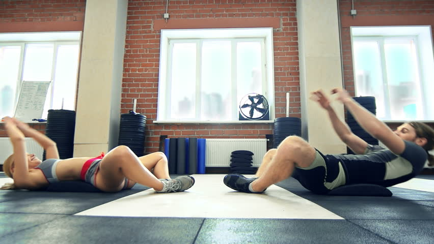 Side view of coach encouraging sportswoman to finish the set of situps in a gym | Shutterstock HD Video #9041584