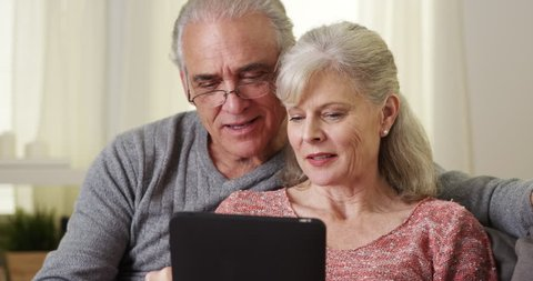Mature couple using tablet on couch