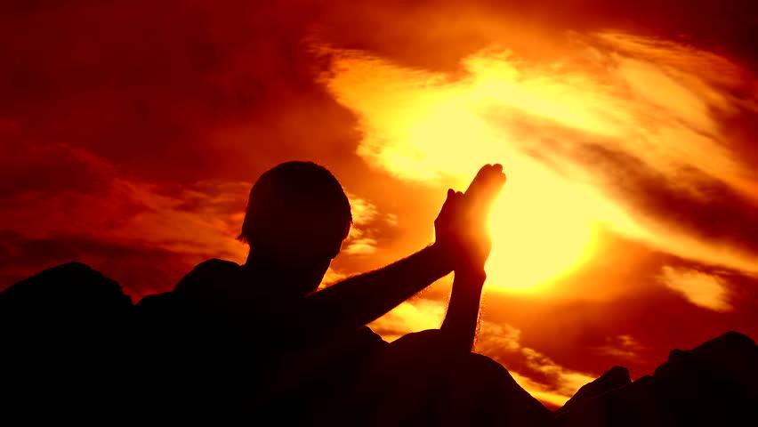 Silhouetted figure kneels on rocky mountaintop, prays, hands lit by glowing, yellow setting sun, striking orange-red background. 4K UHD 3840x2160 | Shutterstock HD Video #9081668