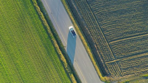 Flying vertically above car driving on road 4K. Aerial shot from top of car vehicle driving on countryside with green fields on both side.