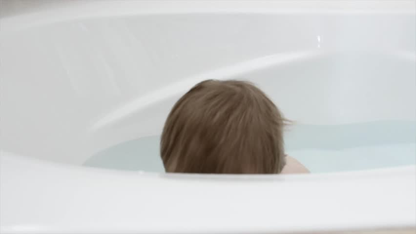 A cute little toddler boy splashing around in the bathtub in his house | Shutterstock HD Video #9118232