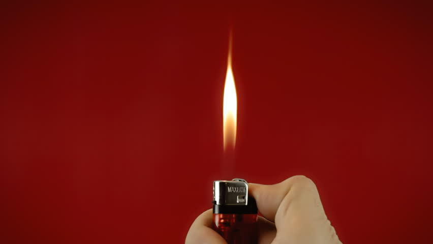 Operating a cigarette lighter. Colorful close-up shot on red background.