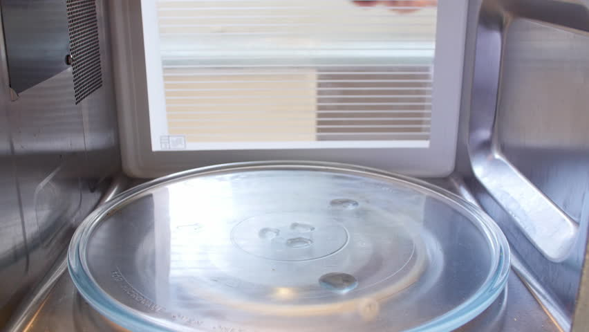 Woman opens door of microwave oven before putting TV dinner inside to cook - speeded up sequence of food cooking. Shot on Sony FS700 at a frame rate of 25 fps