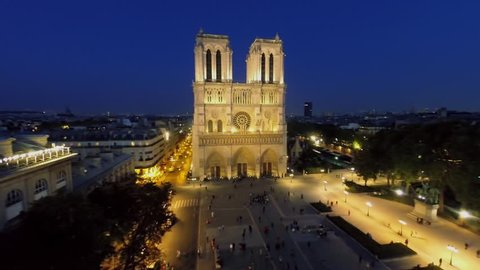Cathedral Notre Dame de Paris on square with many people at autumn evening. Aerial view