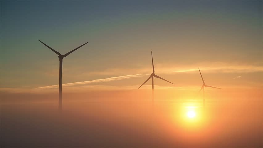 Wind turbines slowly spinning during a foggy, spring sunrise.