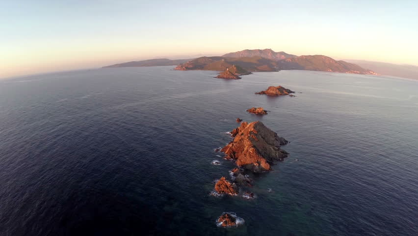 Flight over the sea and islands at sunset, Ajaccio area, Corsica, France. Aerial panoramic view. Archipel des Sanguinaires.