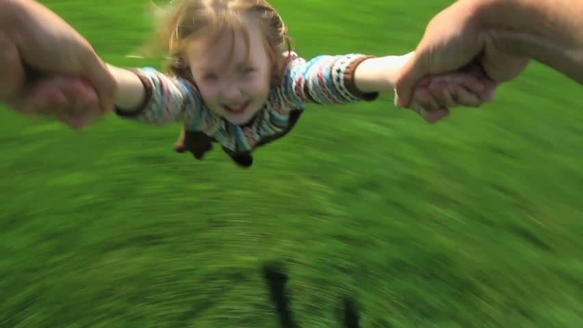 Point-of-view shot of a father spinning his young daughter around in their yard