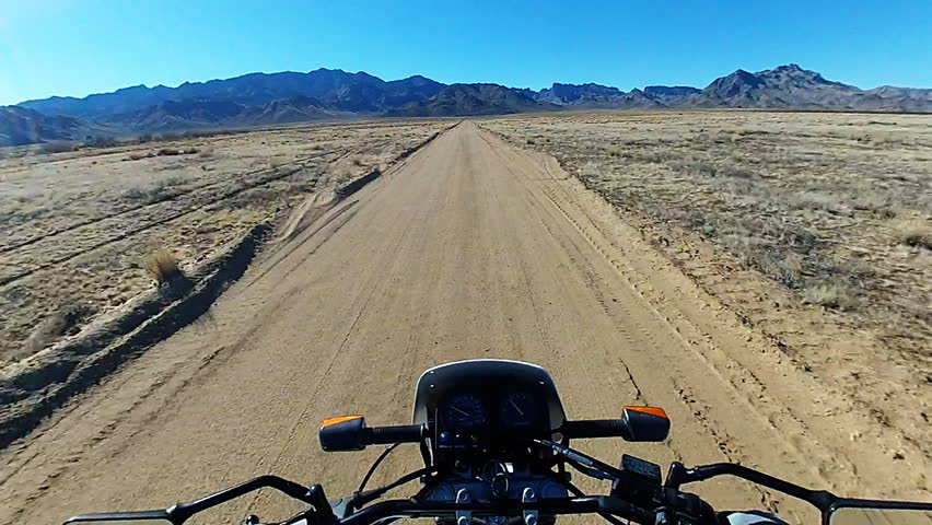 Time lapse shot of the viewpoint of a motorcycle rider speeding on a dirt road in the desert. The handlebars can be seen here bouncing around over the rough terrain in fast motion.