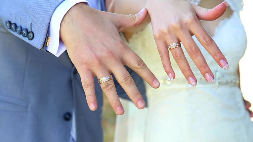 Bride And Groom Showing Gold Wedding Rings On Their Fingers. Male And  Female Hands With