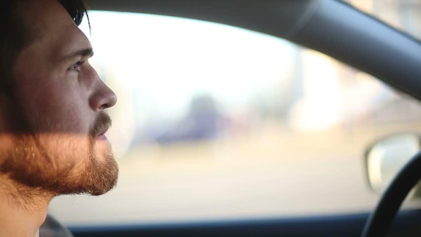 A man drives a car. Close up profile shot