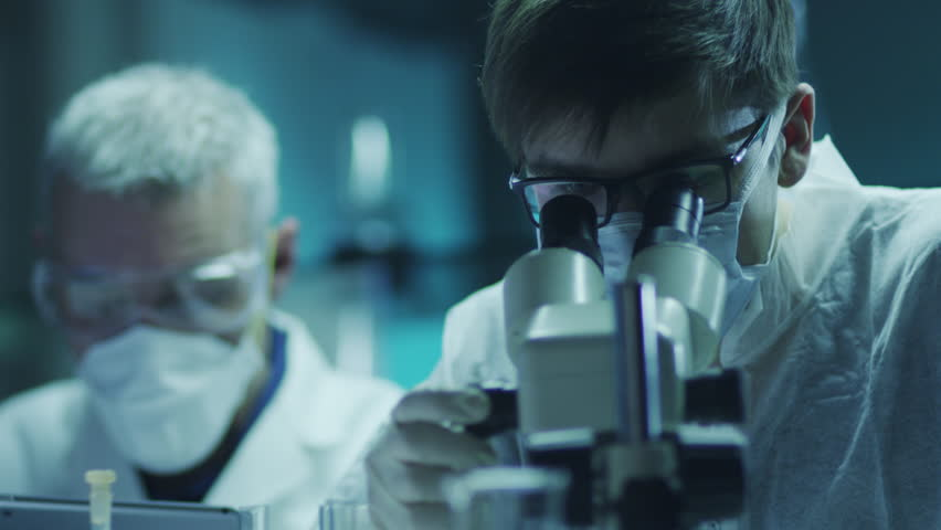 Team of Scientists are Doing Biological Researches Under Microscope and Writing Data into Tablet.  Shot on RED Cinema Camera in 4K (UHD).